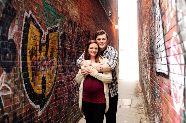 smiling pregnant couple in alleyway