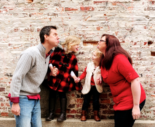 family goofing around in front of brick wall