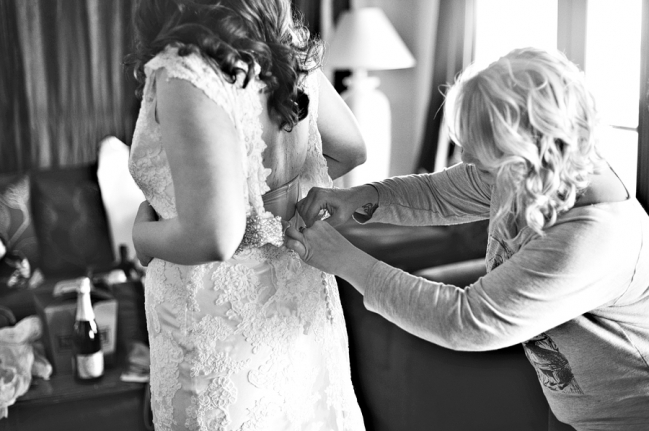 bridesmaid helping the bride with her dress